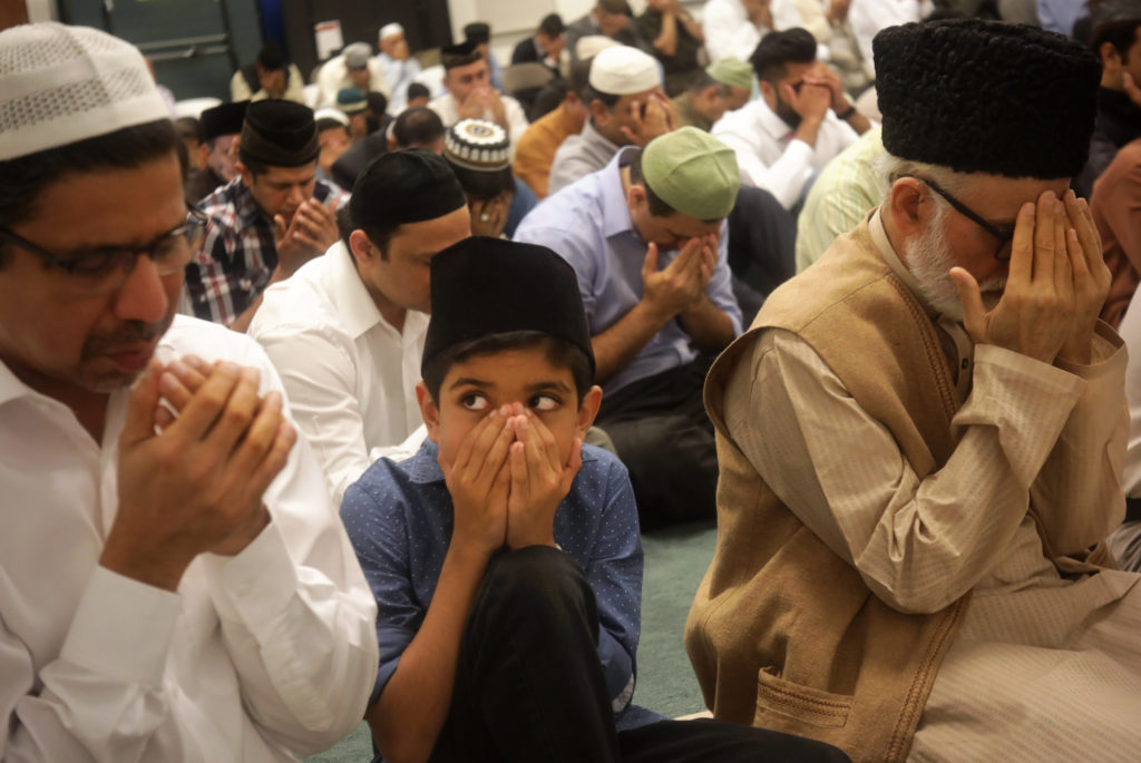 Riyaz Muhammad, left, prays as 9-year-old Aiden Muhammad watches during a prayer service at the Baitul Ikram Mosque in Allen, TX, on Sep. 1, 2017. (Jason Janik/Special Contributor)