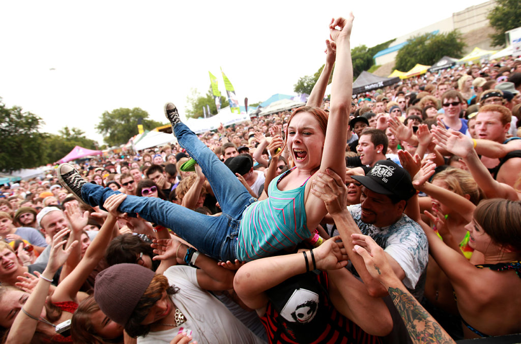 A fan crowd surfs as the audience cheers during the Warped Tour at Superpages.com Center in Dallas, TX, on Sunday, July 5, 2009.